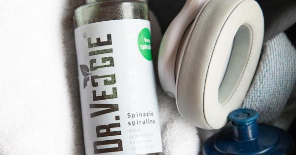 Spinazie groentesap van Dr.Veggie met een koptelefoon en sportbidon
